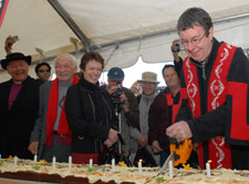 Mayor Garry Moore uses a chain saw to cut the 150th birthday cake, watched by Bishop David Cole, Rik Tau, Ngai Tahu and Mayoress Pam Sharpe.