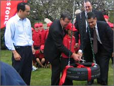 Mayor Garry Moore accepting, on behalf of the city, a tyre swing presented to the children of Christchurch by Firestone Ltd, to celebrate the production of the 35 millionth tyre made at the Firestone factory in Papanui.